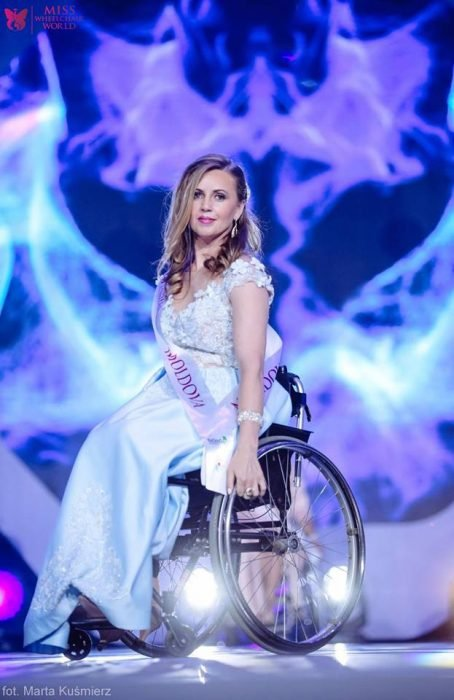 chica en vestido blanco usando silla de ruedas