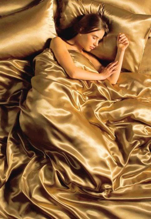 Chica durmiendo en sabanas de seda