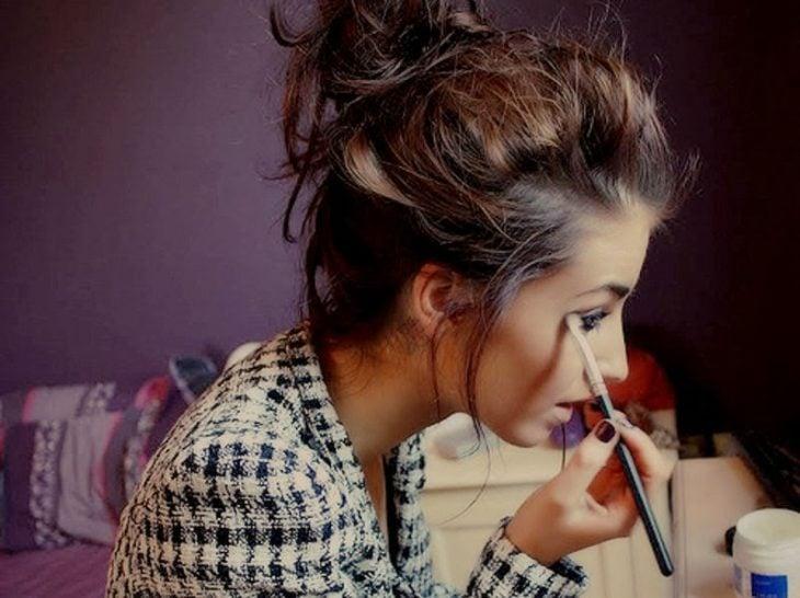 Chica maquillando sus ojos