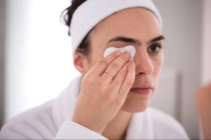 Chica desmaquillando sus ojos con aceite