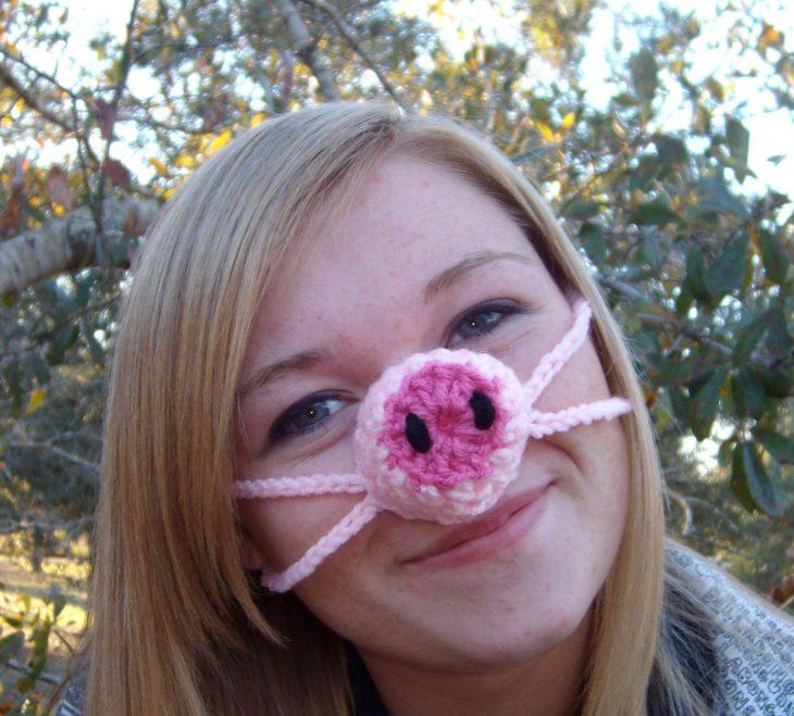 chica cubriendo su nariz del frío