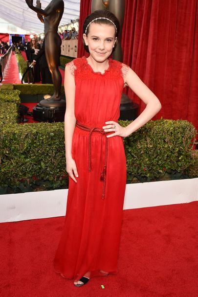 Millie Bobby Brown usando un vestido rojo estilo griego