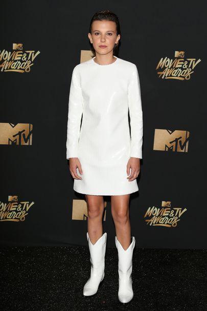 Millie Bobby Brown usando un vestido blanco con botas vaqueras