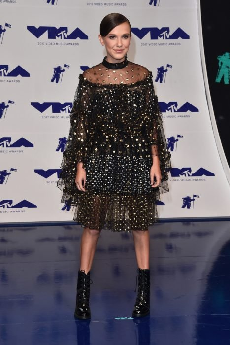 Millie Bobby Brown usando un vestido negro con estoperoles dorados
