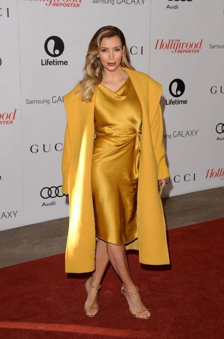 Kim Kardashian usando un vestido amarillo de satín y un abrigo color mostaza