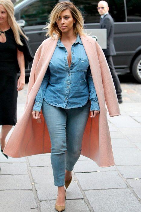 Kim kardashian usando mezclilla y un abrigo roa oversize