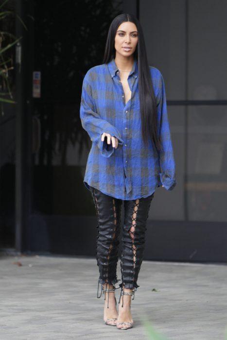 Kim Kardashian usando una camisa de leñador y pantalones negros