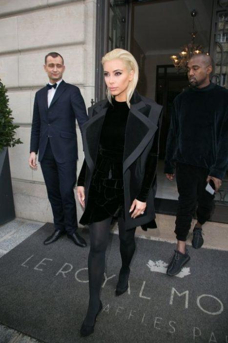 Kim kardashian usando un traje y abrigo de color negro