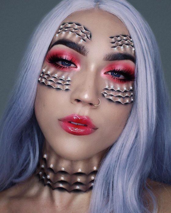 Chica haciendo un maquillaje de fantasia en su rostro