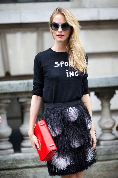 Chica usando una falda de plumas y una blusa en color negro