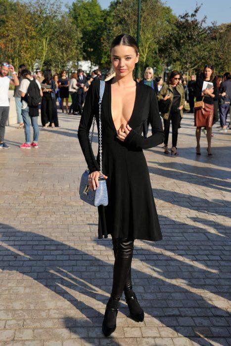 Miranda Kerr usando un vestido negro con escote profundo y botas negras