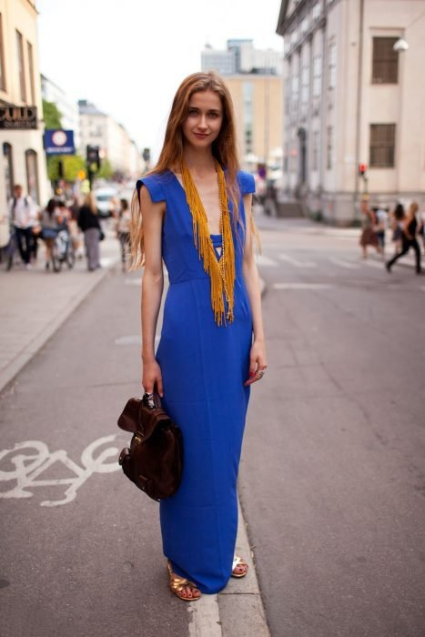 Chica usando un vestido azul y largo con un collar amarillo