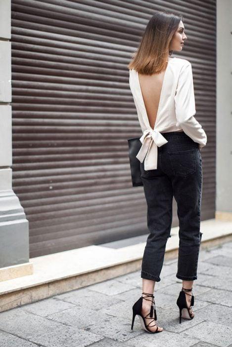 Chica usando una blusa blanca con escote en la espalda