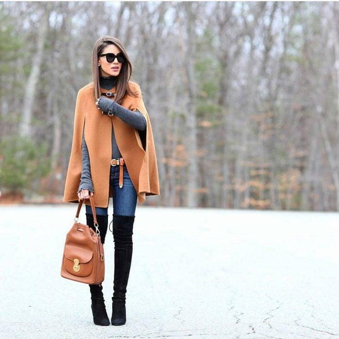 mujer con botas altas y poncho café