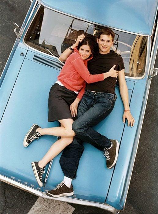pareja de novios recostados en un carro
