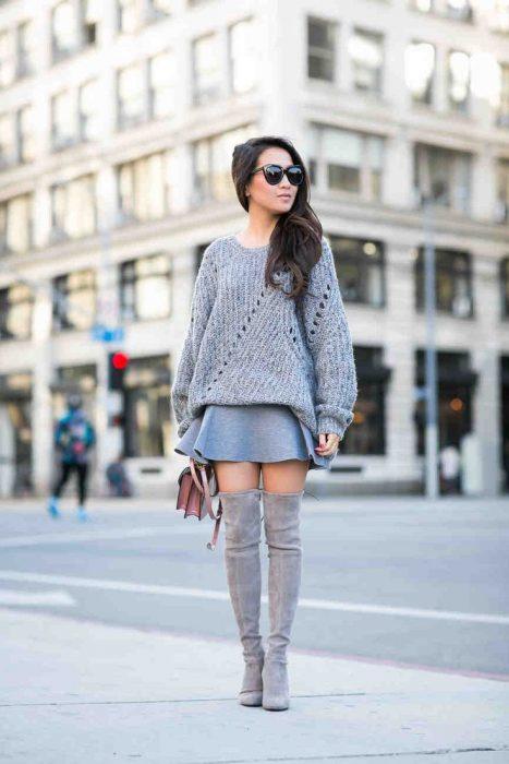 Chica usando una falda gris con botas y sueter oversize