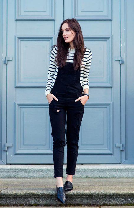 Chica usando un overol negro con una blusa a rayas y mocasines negros