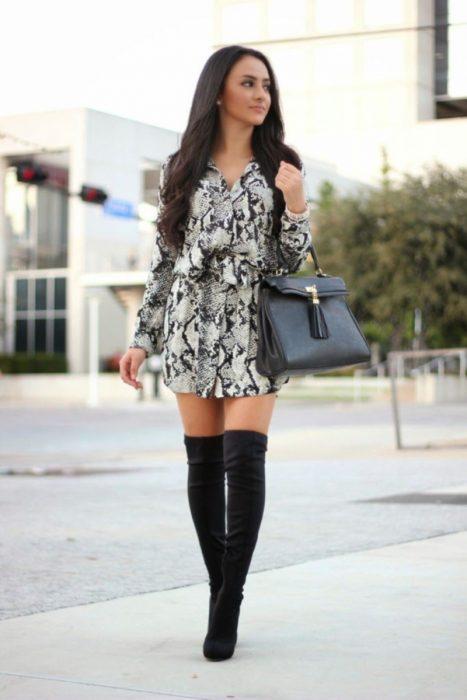 Chica usando un vestido estampado con botas largas