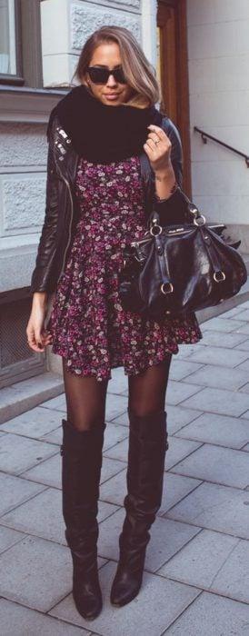 Chica usando un vestido con estampado floral botas y chaqueta negra