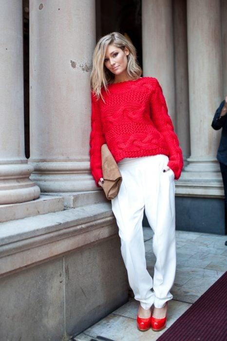 Chica usando un pantalón blanco, suéter rojo y zapatos rojos
