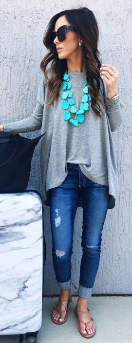 Chica usando una blusa gris con un collar color azul