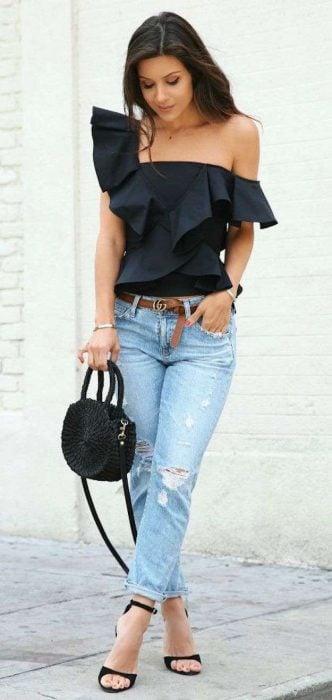 Chica usando un outfit con jeans y blusa negra