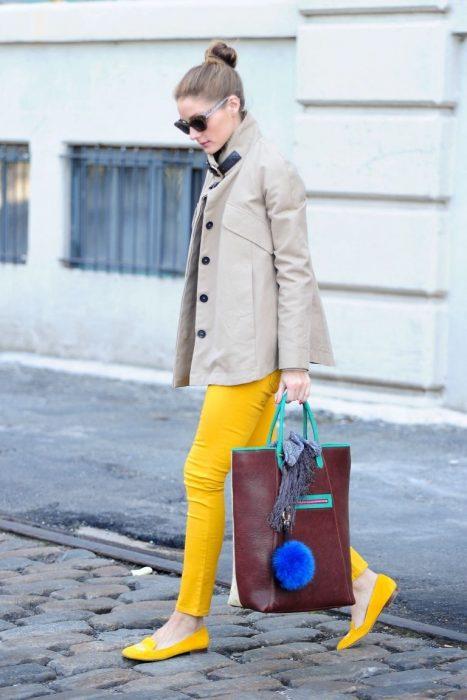 Chica usando un pantalón y zapatos amarillos un trench coat y una bolsa color café