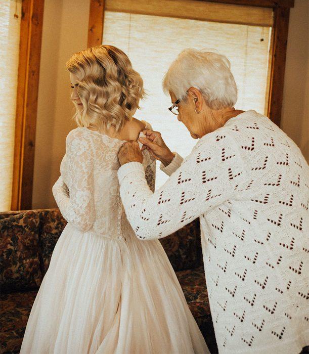 señora abrochando el vestido de su nieta