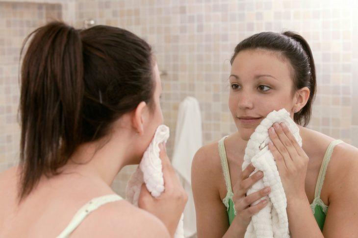 chica lavando su rostro