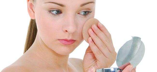 Chica aplicándose polvo translucido