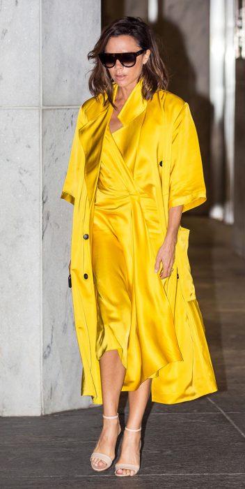 Victoria Beckham usando un vestido amarillo y un trench coat de la misma tela