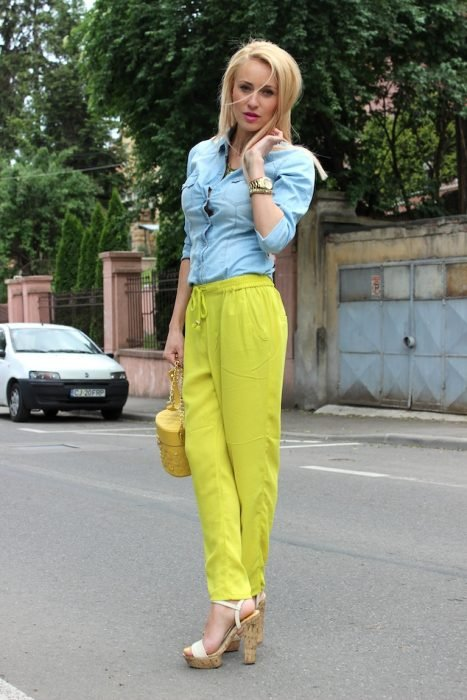 Chica usando un pantalón amarillo limón y una blusa de mezclilla
