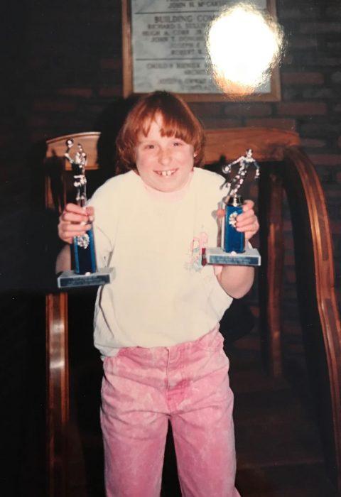 niña sosteniendo un trofeo