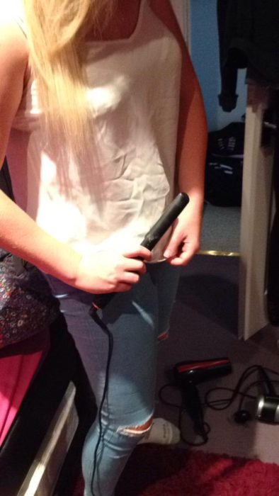 chica planchando su ropa con la tenaza del cabello
