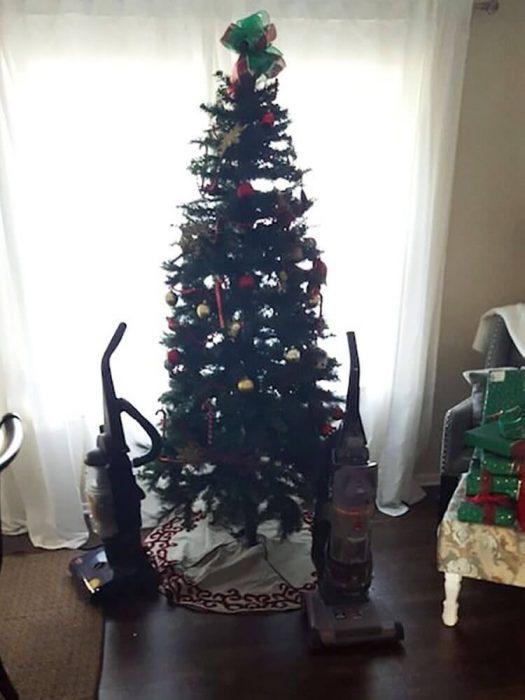 arbol de navidad con dos aspiradoras enfrente