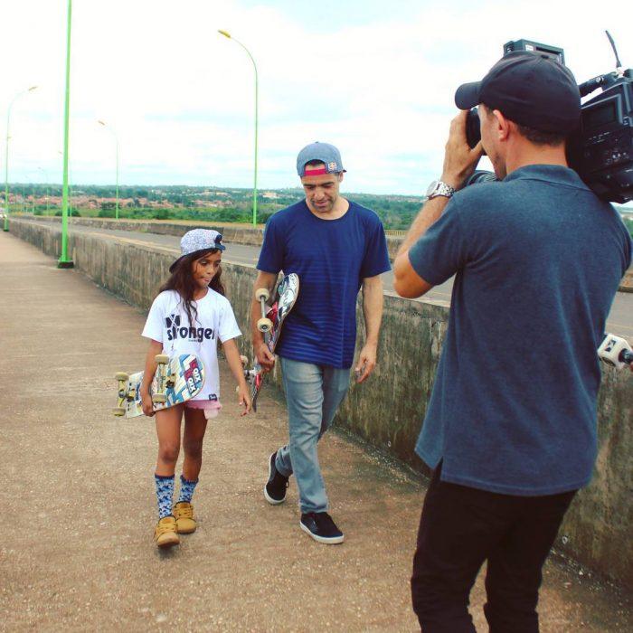 niña cargando patineta caminando