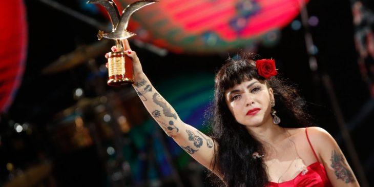 mujer con trofeo en la mano y tatuajes
