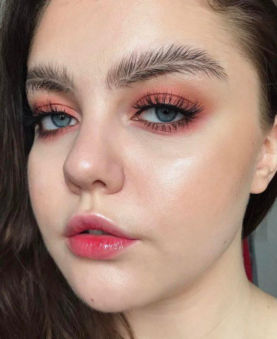 Chica con las cejas en forma de plumas despeinadas