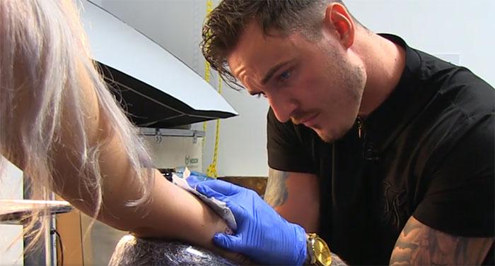 chico tatuando el brazo de una chica