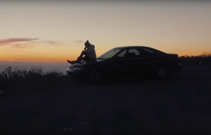 Chica sentada sobre su auto viendo hacia el horizonte