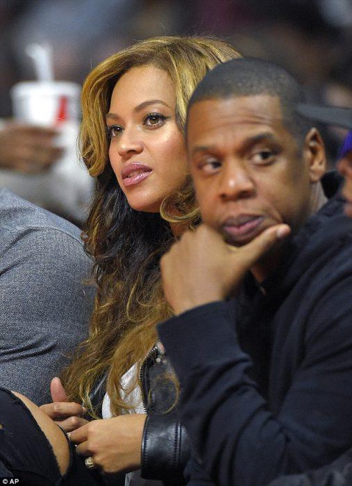 Jay z y Beyoncé sentados durante un juego de basketball