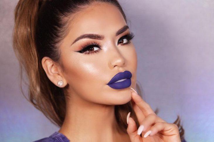 Chica usando un labial color morado mate con iluminador