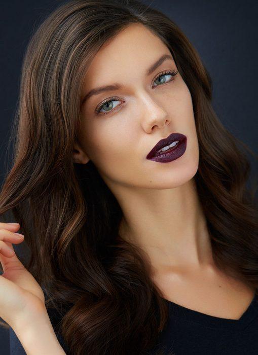 Chica usando un labial de color morado obscuro con un maquillaje ligero