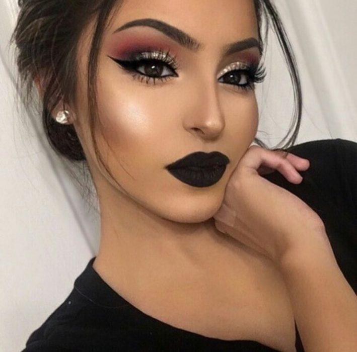 Chica usando una sombra de ojos brillante con unos labios color verde oscuro mate