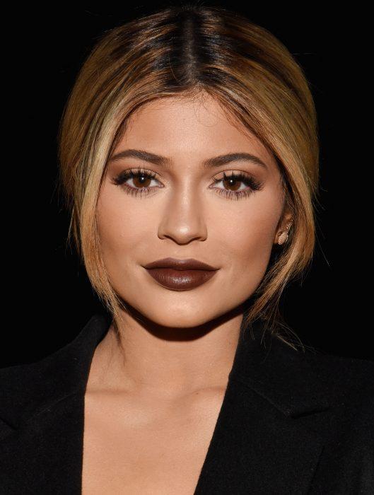Kylie Jenner en el desfile de Vera Wang usando un traje y labios color café