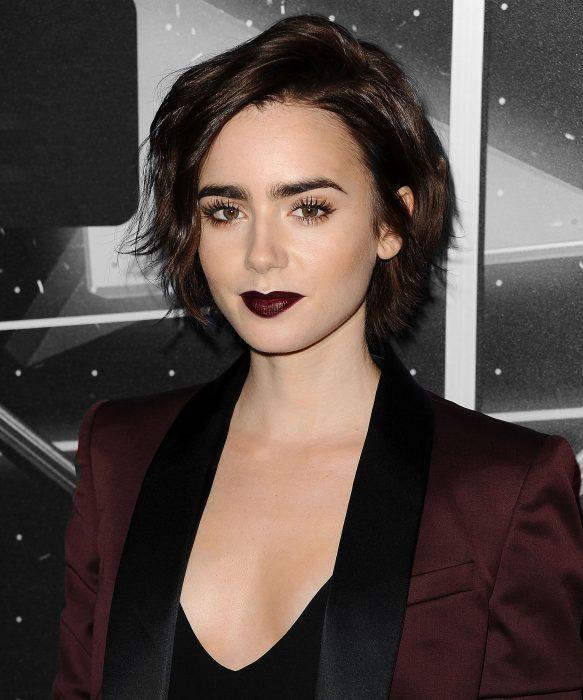Lilly Collins usando un labial negro con un traje color vino