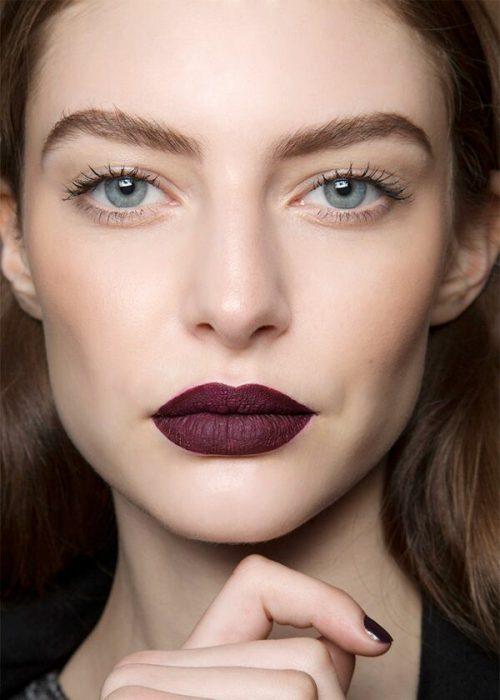 Mujer usando un labial color rojo en tono mate