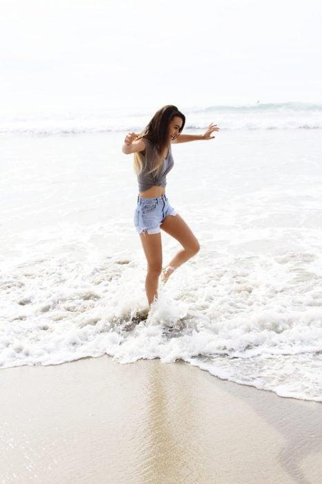 Chica bailando en la playa