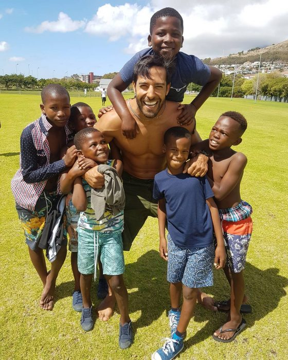 hombre jugando con niños al fútbol