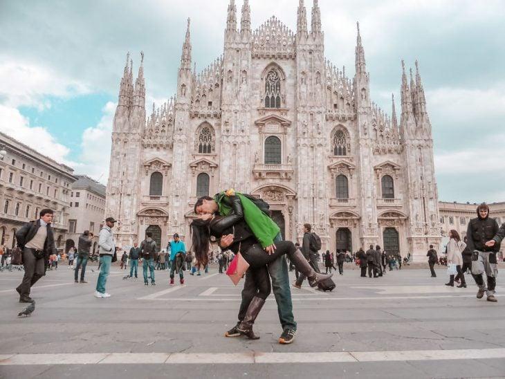 Pareja tomandose una foto en medio de una plasa de Milán, Italia